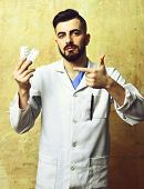 Doctor With Beard And Assured Face Expression Pointing Pills poster