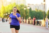 Overweight young woman jogging in the street. Weight loss concept poster
