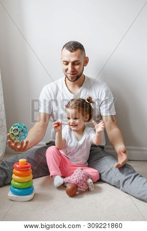 poster of Young Caucasian Father Playing With Child Girl. Male Man Parent Entertains Toddler Daughter Sitting