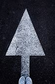 White Arrow Forward On The Asphalt And Feet In White Sneakers, Standing At The Base Of The Arrow. Th poster