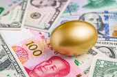 Shiny Golden Egg On Pile Of Chinese Yuan And Us America Dollar Banknotes Money Metaphor Of Finding T poster