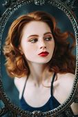 A portrait of a gorgeous beautiful young woman looking through the frame of the mirror. Beauty, cosm poster