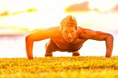 Fitness fit male man doing pushups workout outdoor in sunset summer beach flare. Handsome strong mal poster