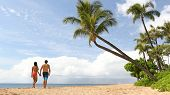 Beach summer vacation couple walking under palm trees in bikini and swim trunks. poster