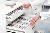 Ophthalmologist Hands Close Up, Choosing Glasses From A Drawer In The Optical Store . poster