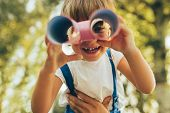 Closeup Image Of Cute Little Boy Playing With A Binoculars Searching For An Imagination Or Explorati poster