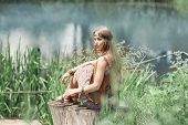 Beautiful Hippie Girl Sitting On A Stump And Looking At The Pond poster
