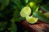 Lime Slices And Mint Leaves On An Old Wooden Background. poster