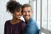 Loving multiethnic couple embracing and sitting near window. Happy girlfriend and smiling boyfriend  poster