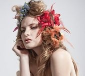 Face of a beautiful woman with summer flowers in her hair