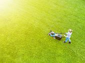 Beautiful Girl Cuts The Lawn. Mowing Lawns. Aerial View Beautiful Woman Lawn Mower On Green Grass. M poster