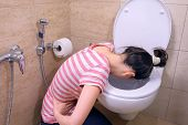 Sick Young Woman Is Vomiting In Toilet Sitting On The Floor At Home, Food Poisoning Symptom, Side Vi poster