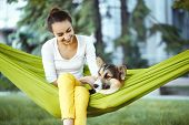 Smiling Young Woman In Green Hammock With Cute Dog Welsh Corgi In A Park Outdoors. Beautiful Happy F poster