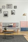 Fashionable Settee With Pillows In Bright Living Room Interior With Pastel Pink And Blue Painting poster