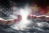 USA vs China. Two boxing gloves punch. Flags on the cloudy sky. International competition, trade war poster