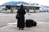 Nun Traveling With Suitcases And Luggage. A Woman In Black Monastic Clothes Is Waiting For A Bus On  poster