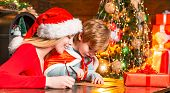 Mom And Kid Play Together Christmas Eve. Happy Family. Family Holiday. Mother And Little Child Boy A poster