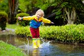 Child Playing In Puddle. Kids Jump In Autumn Rain poster