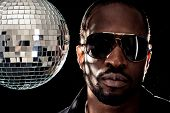 Young cool black man with disco ball over black background.