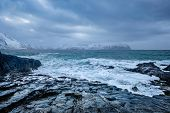 Waves of Norwegian sea crushing at rocky coast in fjord. Vikten, Lofoten islands, Norway poster