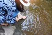 Female Spa Feet Cleaning With Stone On The Nature River Stream / Woman Having Her Feet Scrubbed , Sp poster