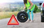 Woman In Reflective Vest Holds Wheel Wrench And Rolls The Spare Wheel. Spare Wheel Replacement. Punc poster