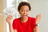 Young african american woman holding bank notes of twenty dollars screaming proud and celebrating vi poster