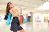 Jovem mulher sorrindo com sacos no centro comercial de compras.