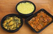 Indian convenience food of chicken massala curry, saag aloo and pliau rice.