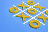 Yellow Plastic Crosses And A Toe And A Ruled Field For Playing Tic-tac-toe On A Blue Background. Con poster