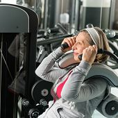 Fitness center senior woman exercise abs muscle on gym machine