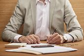 Partial View Of Businessman In Suit Filling In Bankruptcy Form At Wooden Table poster