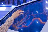 Woman Using Interactive Touchscreen Display Of Electronic Multimedia Kiosk At Technology Exhibition  poster