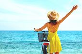 Young Beautiful Woman Enjoying The Sea View With Her Bicycle. poster