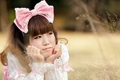 japanese woman in sweet lolita cosplay lying in meadow, tokyo