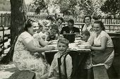 Vintage photo of big happy family dining outdoor (fifties)