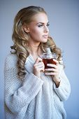 Beautiful young blonde woman in a stylish warm winter top standing daydreaming as she enjoys a mug of hot tea