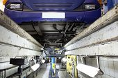 stock photo of boom-truck  - view to repair shop from an inspection pit - JPG