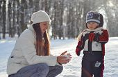 Young Mother Making Snowballs For A Kid On A Winter Walk In The Park