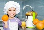 girl  making fresh orange juice with a juice extractor