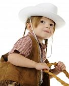 Low angle, closeup image of a preschool cowgirl with her hands on rope reigns.  On a white backgroun