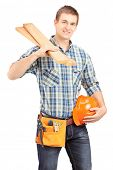 Smiling carpenter holding a helmet and sills isolated on white background