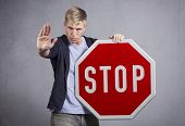 Serious man showing stop gesture with hand as warning while holding stop sign isolated on grey background.