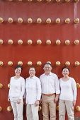 Group of mature people standing next to traditional Chinese door, portrait