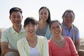 Portrait of smiling multigenerational family sitting on the rocks outdoors, China