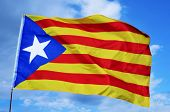 an estelada, the Catalan separatist flag, waving over the blue sky