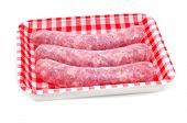 a pile of uncooked pork meat sausages in a plastic tray on a white background