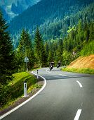 Group of motorcyclists in Alpine mountains, moto racers on curve mountainous road, touring along Europe, travel and tourism concept