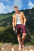 full length picture of a young casual man standing with a hand in his pocket, in the mountains, and