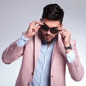 young fashion man taking off his sunglasses while looking into the camera. on a light background